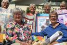 Taradale Village Quilters with a selection of quilts made for charity.