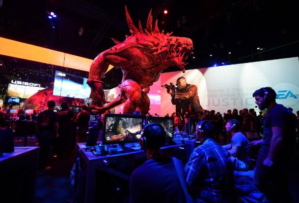 Gamers check out Evolve underneath a statue of a Goliath monster at the Ubisoft booth at E3 2014.