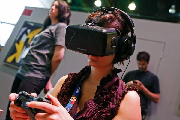 A woman uses the Oculus Rift virtual reality headset at the 2014 Electronic Entertainment Expo.