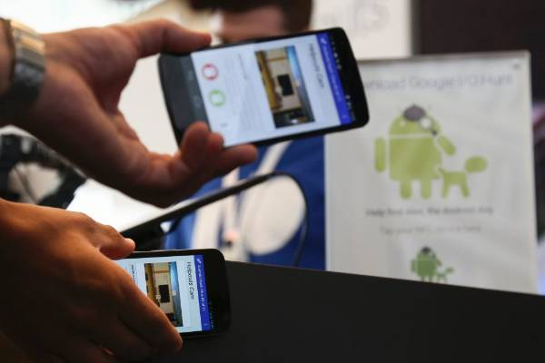 Attendees play a check-in game to win prizes by tapping their NFC-enabled Android smartphones at the Google I/O ...