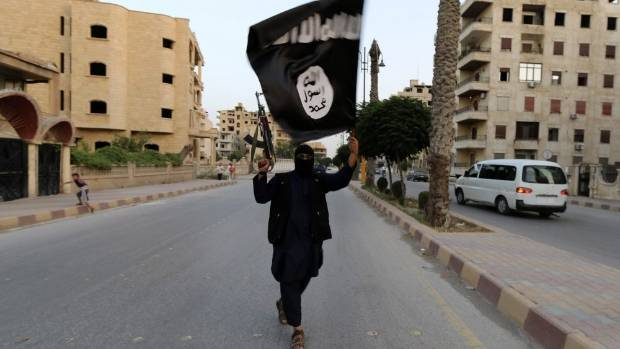 TERROR THREAT: A member of the Islamic State in Iraq and the Levant - the forerunner to the Islamic State - waves an ISIL flag.